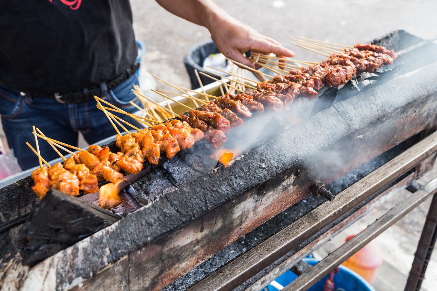 A common sight in hawker centres; vendors fanning the chargrilled bbq satay meat before serving them to customers.